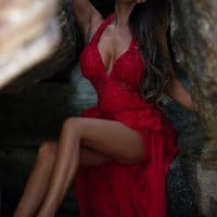 Beautiful Brunette Woman Wearing Nice Makeup and Posing in an Open Red Dress