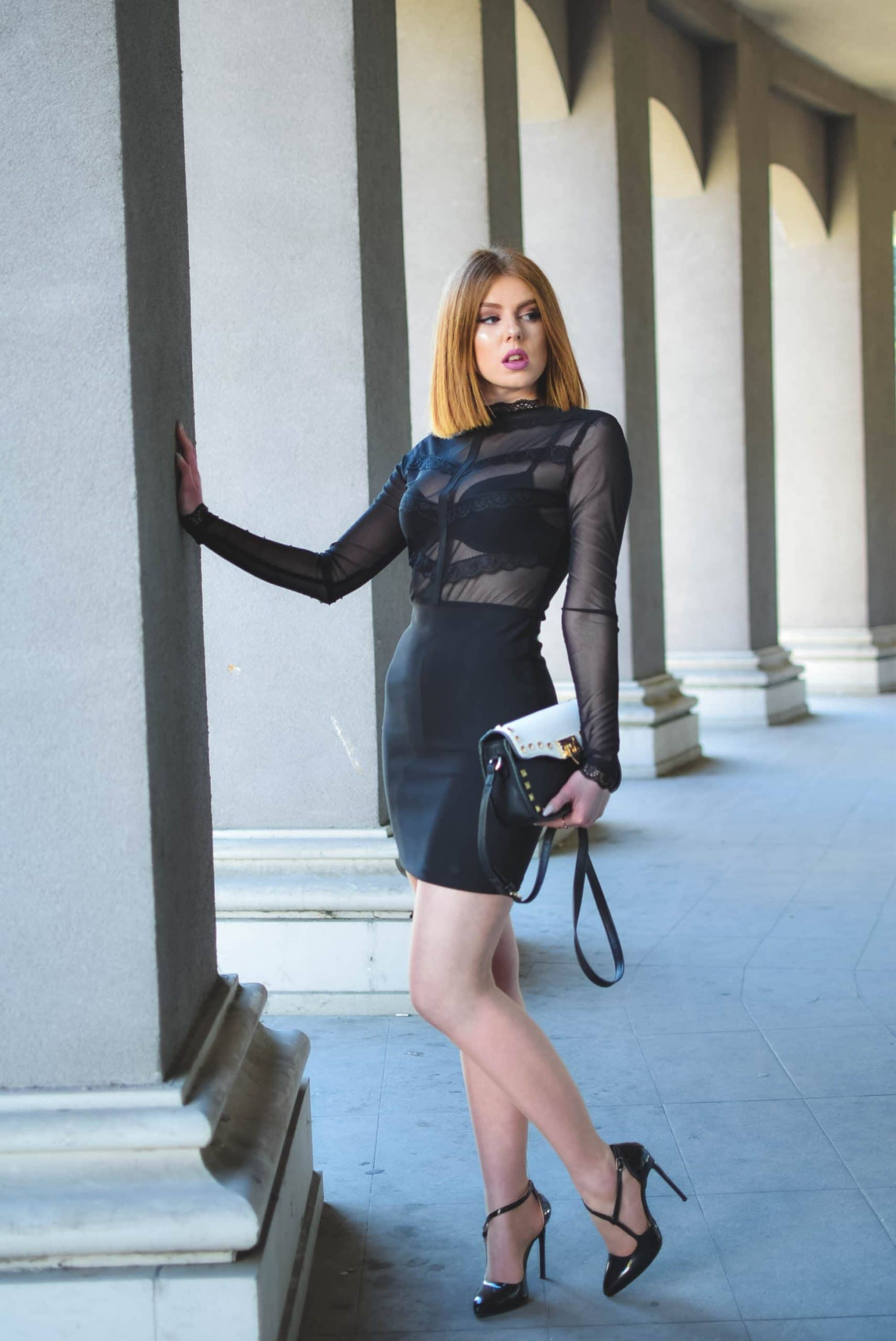 Beautiful Women Wearing a See through blouse showing her black bra, a Classic Black Skirt in nylons and High Heels