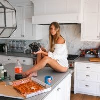 Cute Sexy Blonde Woman Sitting Bare Feet On The Kitchen Counter Showing her tones legs
