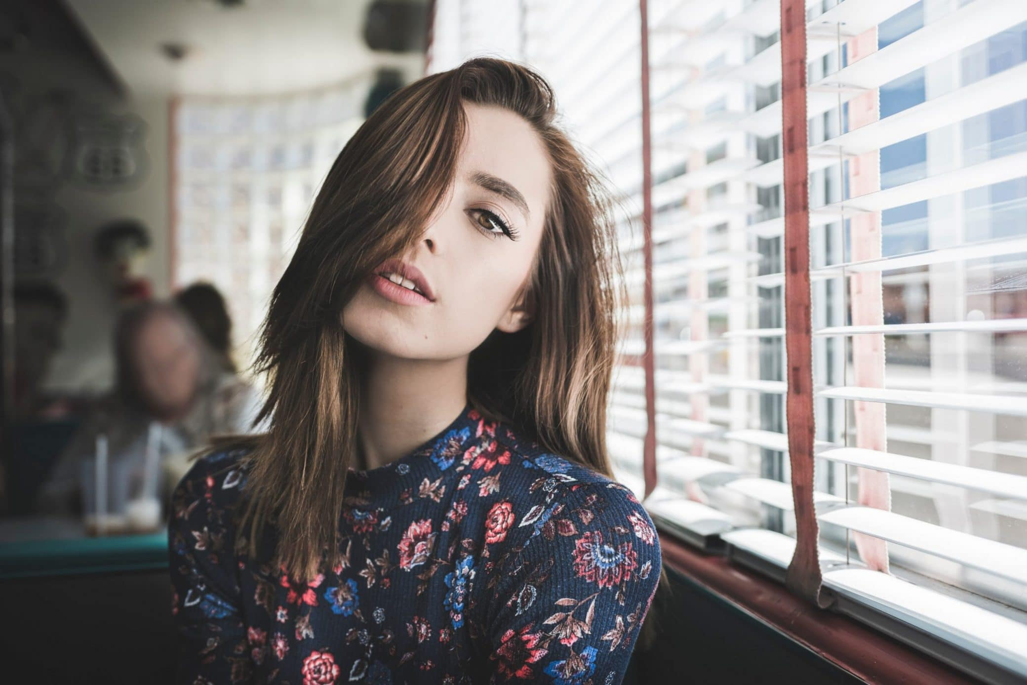 Beautiful Young Woman Sitting in a Diner posing for a portrait