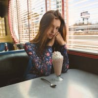 Beautiful Young Woman Sitting in a Diner Drinking a Milkshake