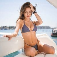 Beautiful brunette woman on a boat wearing a bikini chowing her incredibly fit body and cleavage
