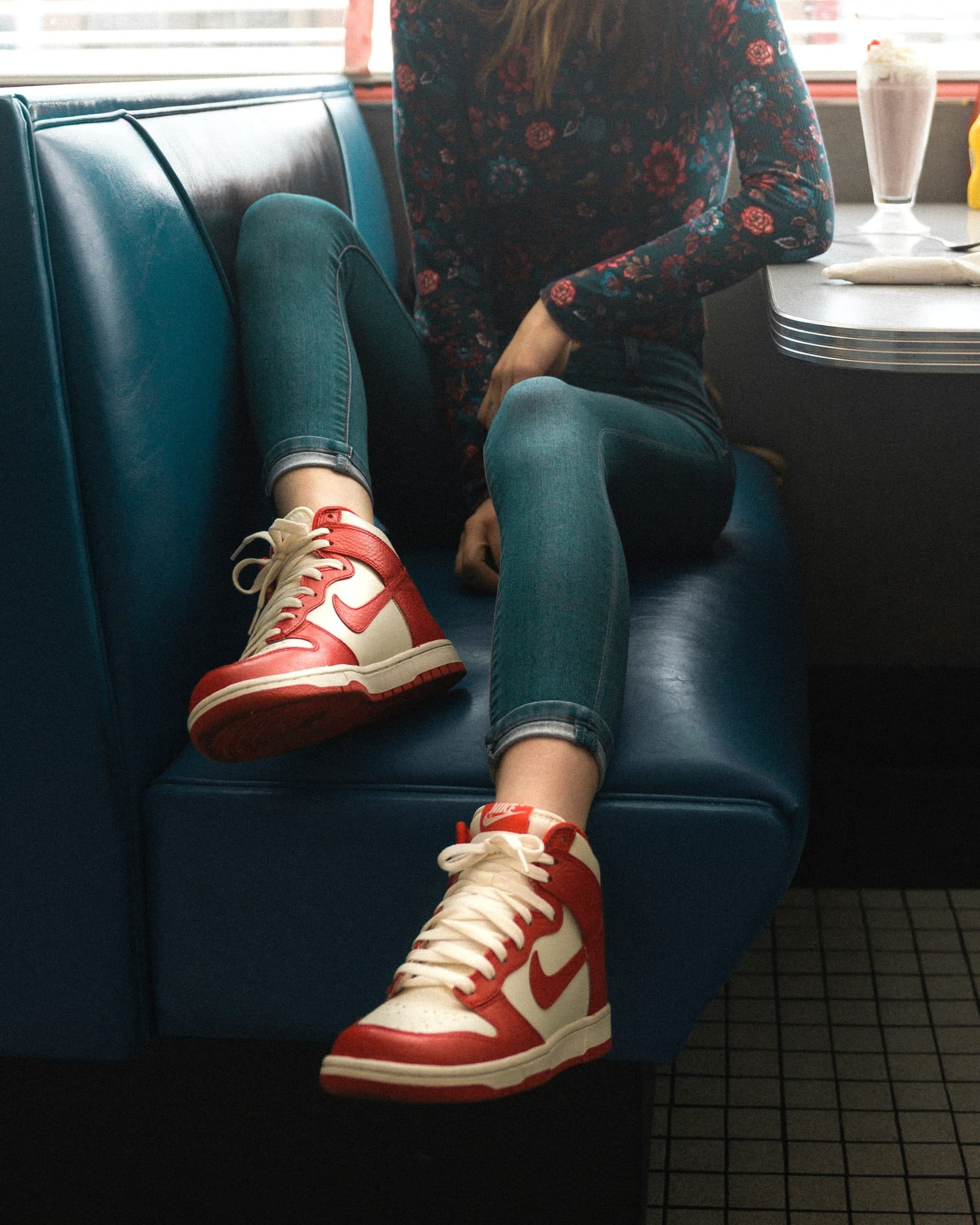 Beautiful Young Woman Sitting in a Diner posing showing her legs un skinny jeans and sneakers