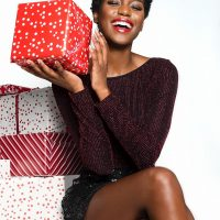 Beautiful black woman smiling wearing short shorts showing her sexy crossed legs holding a Christmas gift
