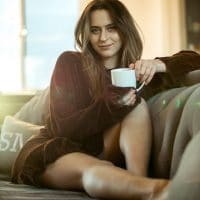 Beautiful woman sitting comfy on a sofa with a cup of coffee and her bare legs showing