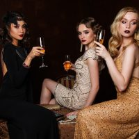 Beautiful young women trio in classy dresses making a toast
