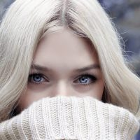 Beautiful Blonde Woman with Blue Eyes in a Knitted Sweater