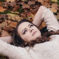 Beautiful woman lying in the autumn leaves