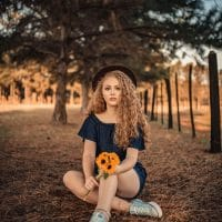 Beautiful woman with curly hair sitting on the ground wearing sneakers