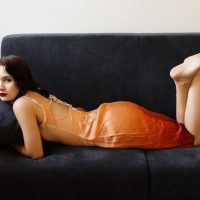 Beautiful young woman lying on a sofa bare foot with her bare legs crossed wearing an orange-red dress
