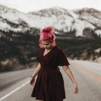 Beautiful pinked haired woman posing on the road wearing a short burgundy dress