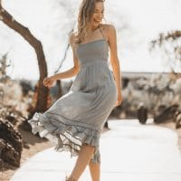 Beautiful woman smiling and dancing wearing a grey dress and open sandals at the park showing her bare legs and feet