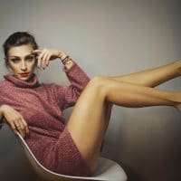Beautiful woman with colourful makeup posing sitting on a chair showing her long legs