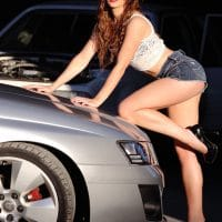 Beautiful woman in heels wearing a white top and short denim shorts in front of a car