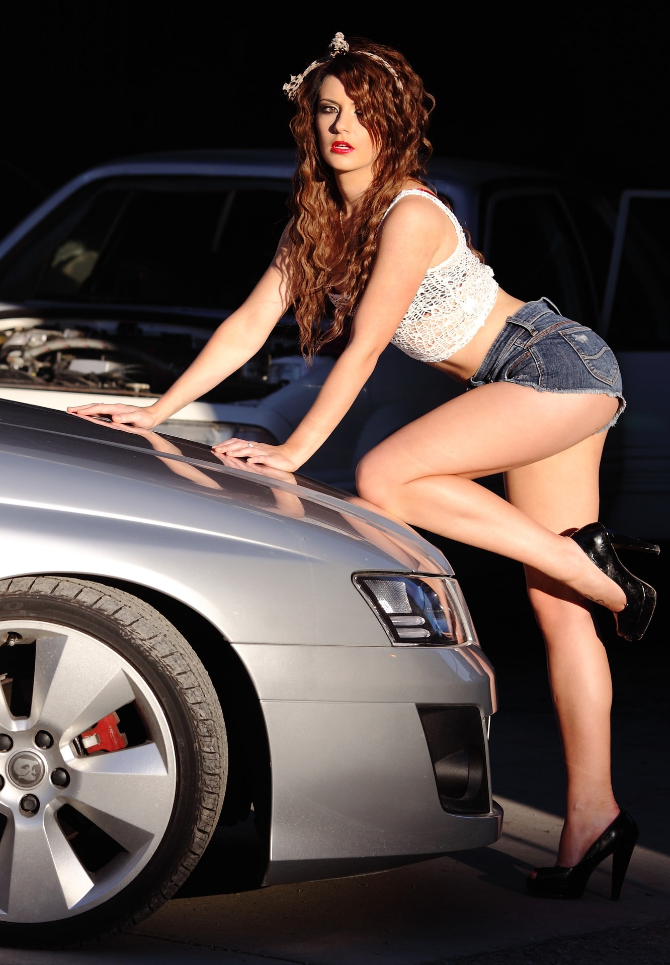 Beautiful woman in heels wearing a white top and short denim shorts in front of a car showing her long sexy legs