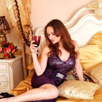Beautiful woman sitting on her bed wearing a purple open dress holding a glass of wine