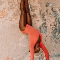 Beautiful woman posing in gymnastic poses in a red bodysuit un front of a wall