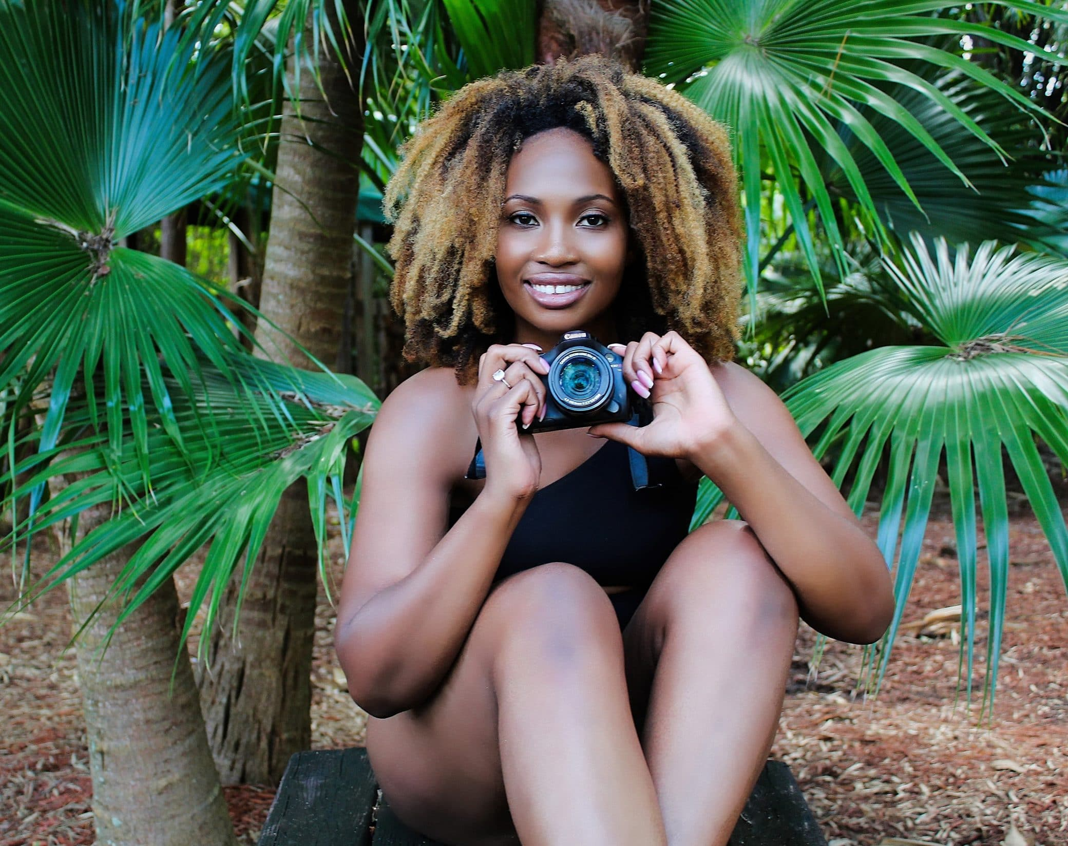 Beautiful black woman posing wearing a swimming suit sitting in front of a palm tree showing her legs