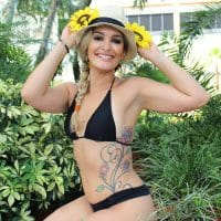 Beautiful blonde woman smiling and posing sitting in the sand wearing a black bikini and a hat with her arms up showing her arm pits and tattoo
