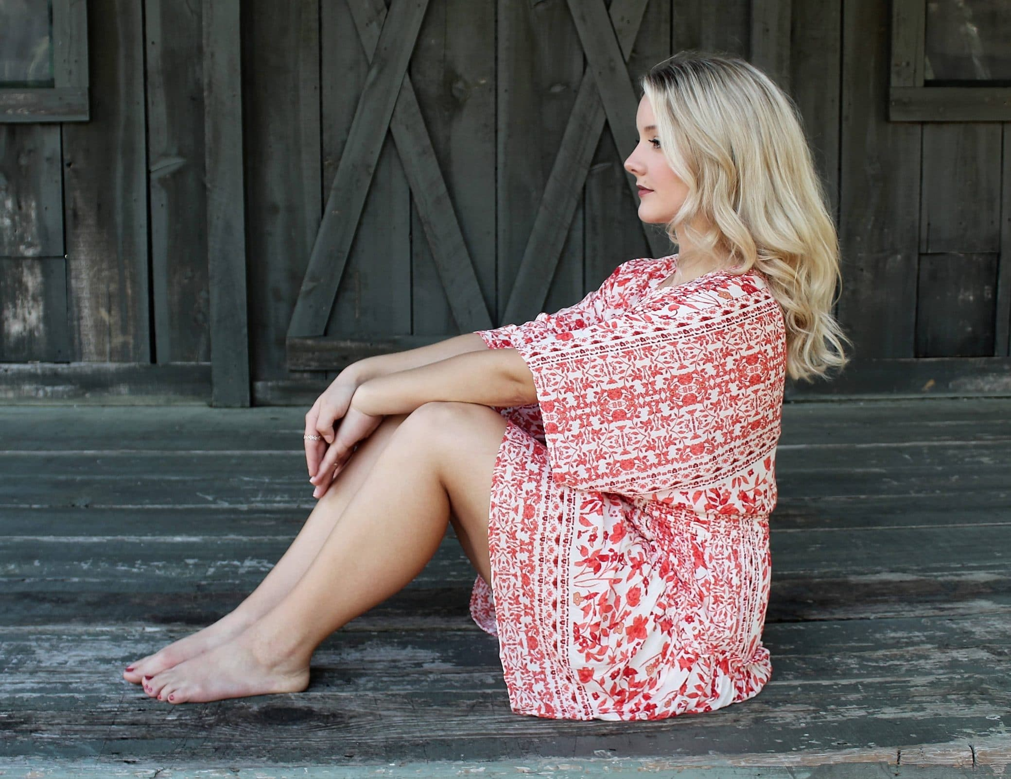 Beautiful blonde woman sitting wearing a summer dress showing her bare legs and feet