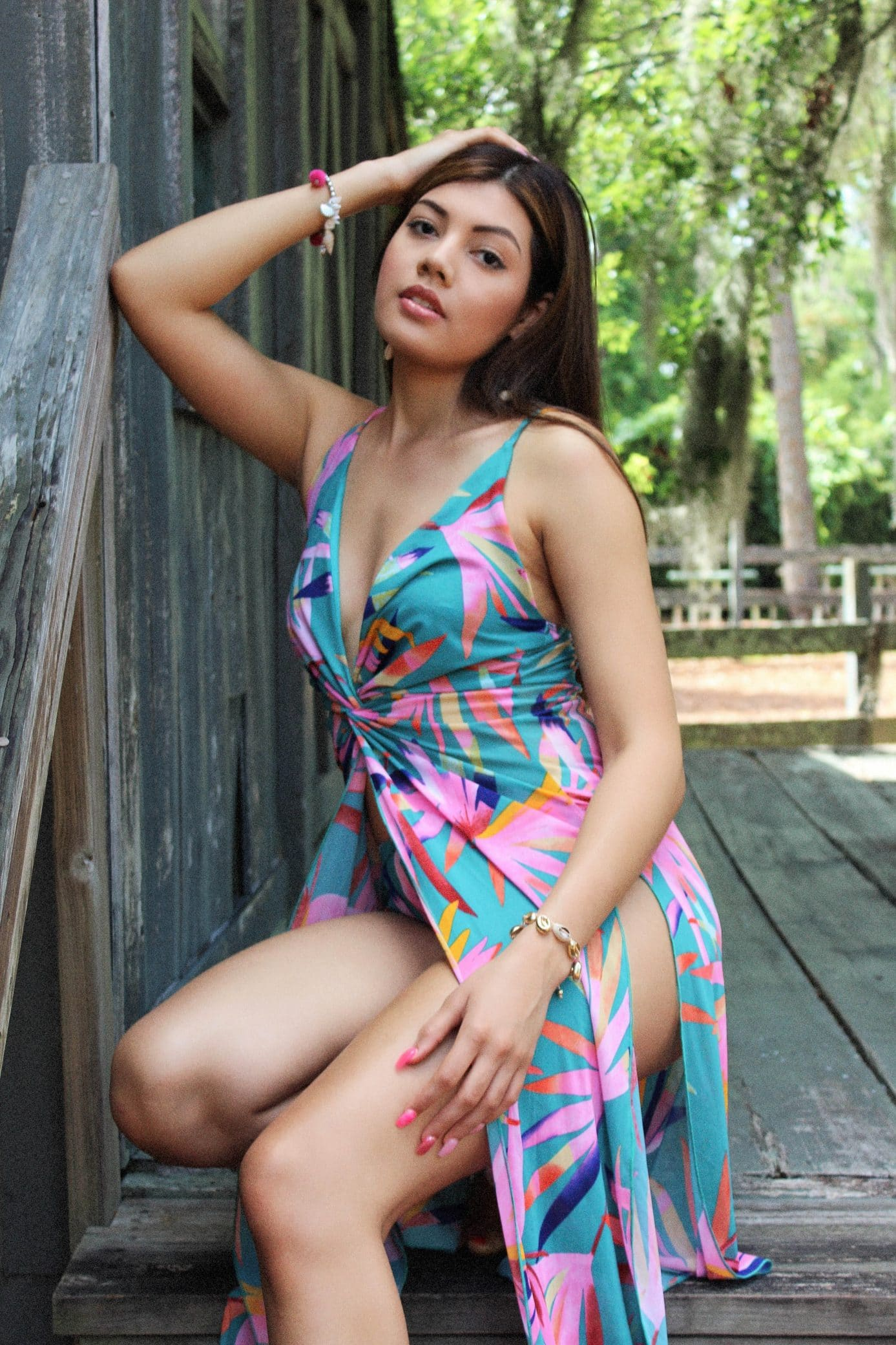 Beautiful woman Bryanna Quintero wearing an open colourful dress and jewelry  sitting with one arm up an red nail polish