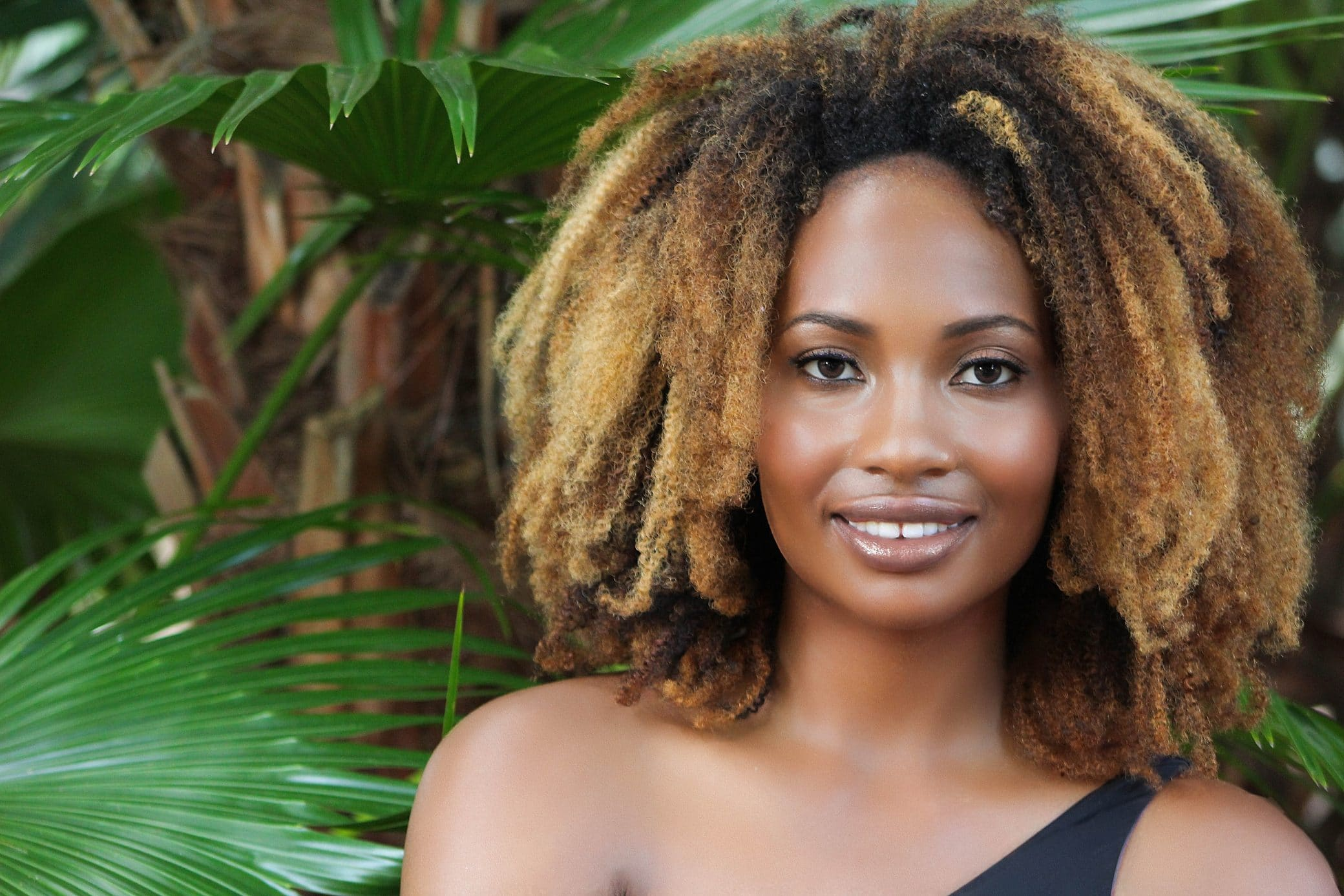 Beautiful black woman portrait smiling posing with palm trees
