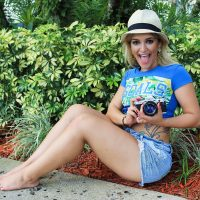 Beautiful tattooed blonde woman taking pictures with her mouth opened wearing a blue top and denim shorts showing her sexy legs and bare feet brazil