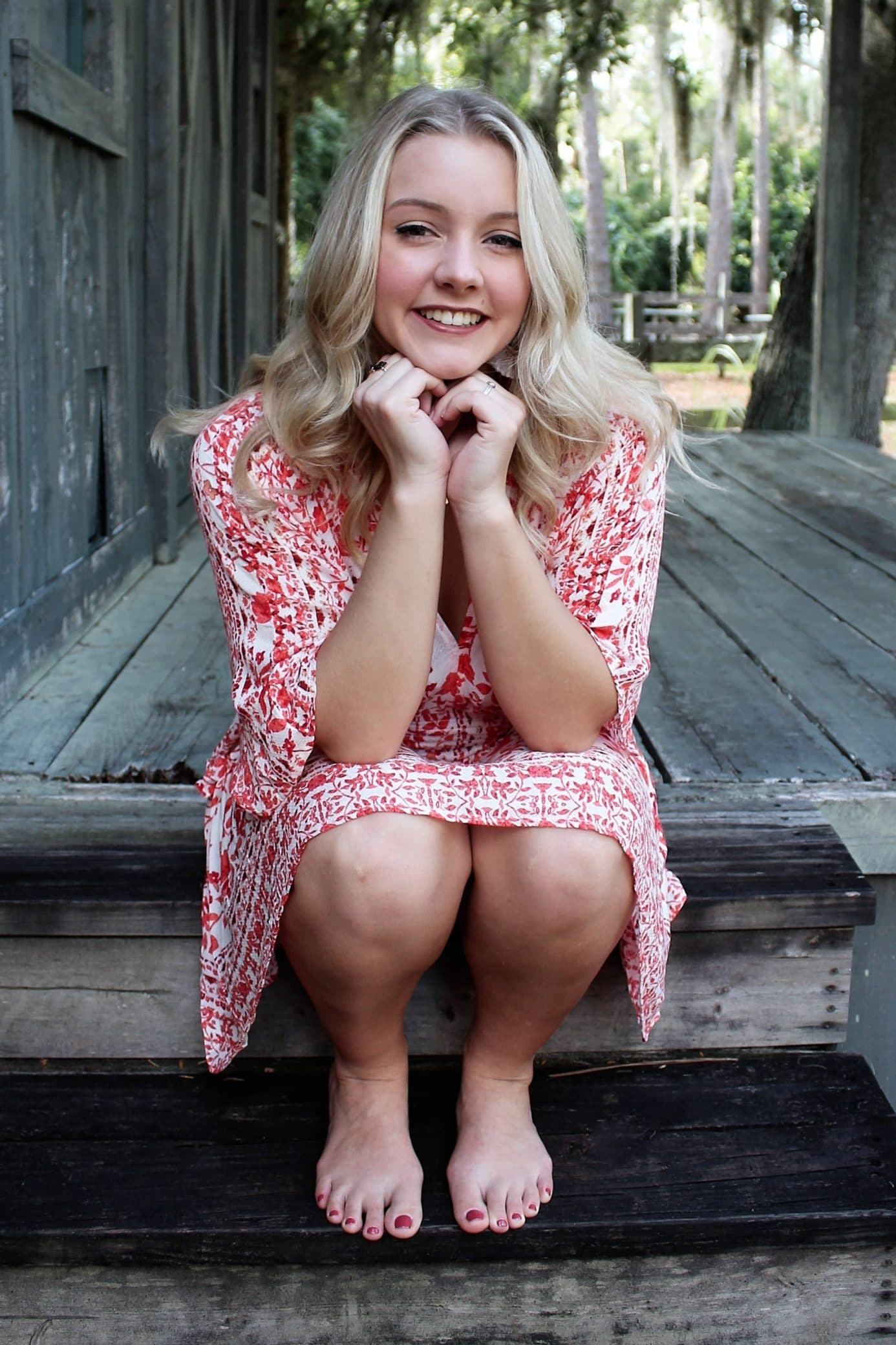 Beautiful blonde woman smiling sitting wearing a summer dress showing her bare legs and feet