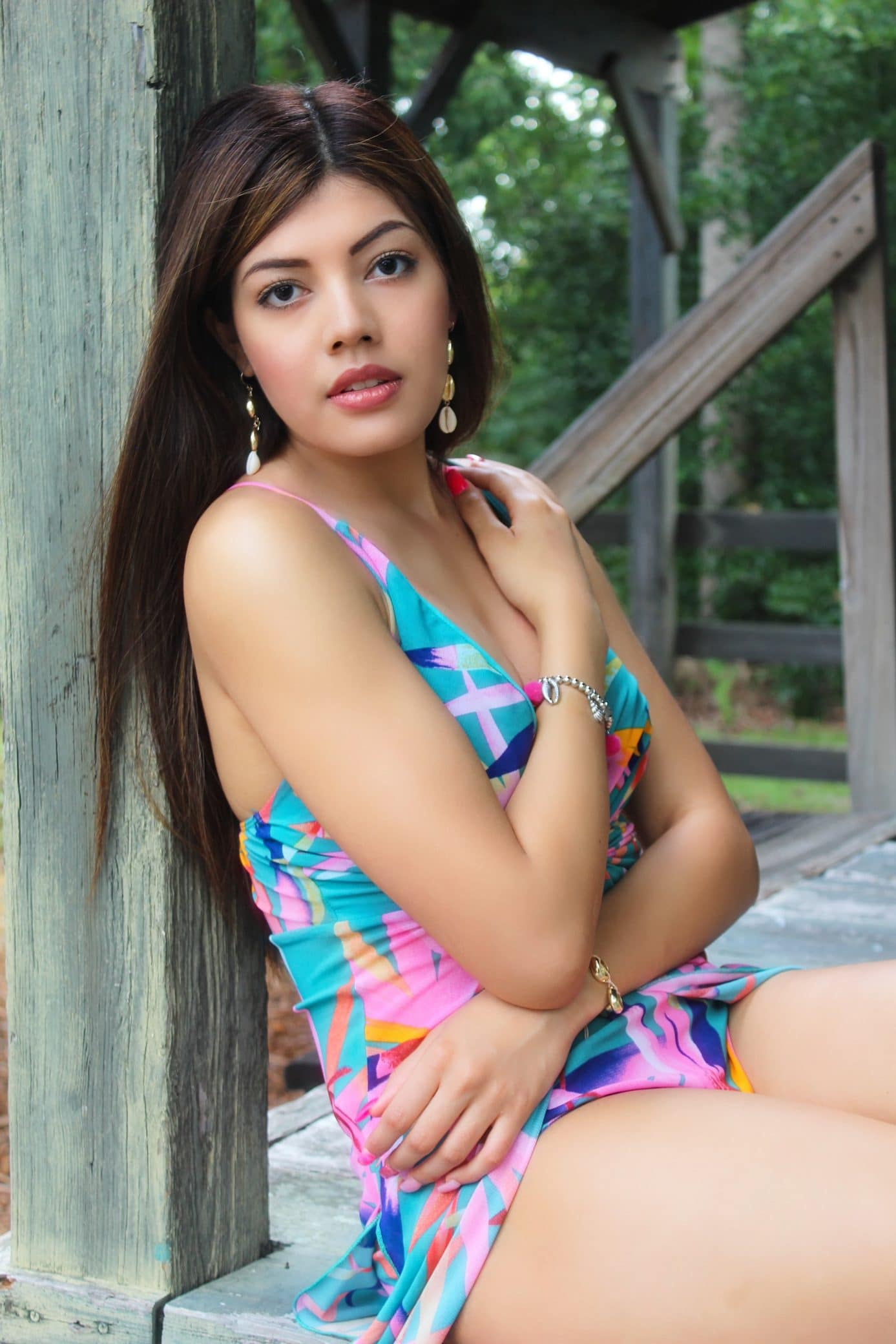 Beautiful woman Bryanna Quintero wearing an open colourful dress and jewelry sitting with her arms on her chest