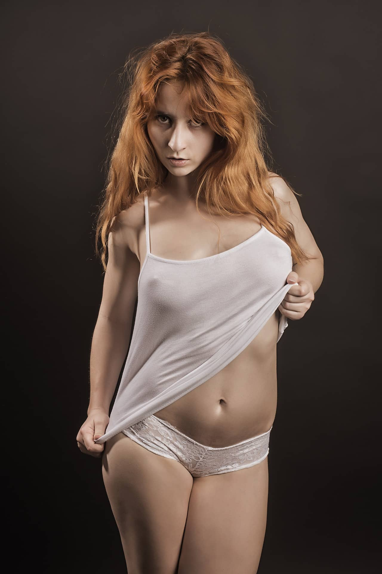 Beautiful redhead woman posing in an artistic photoshoot with her arm up wearing white transparent clothes and lace panties showing belly button