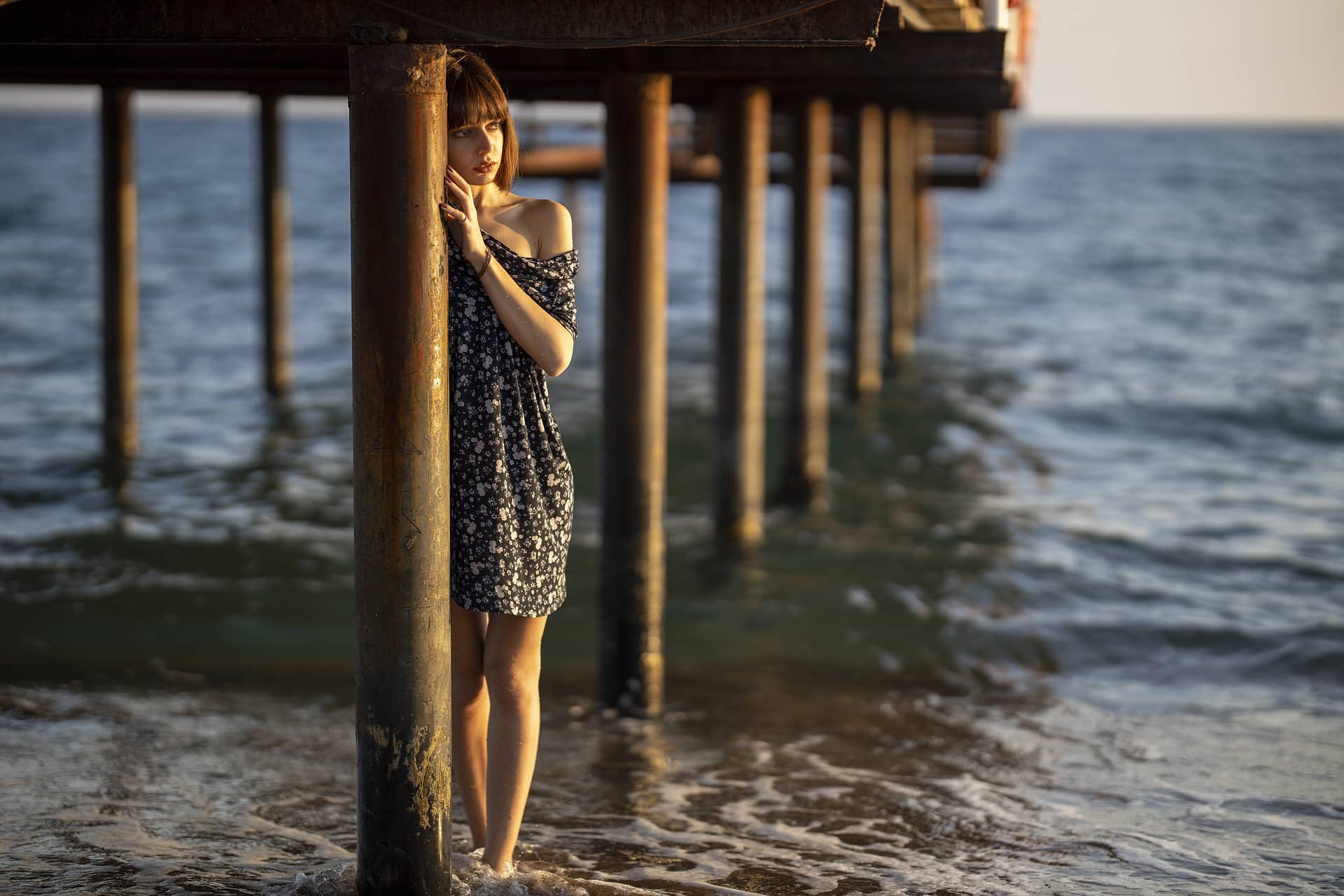 Beautiful woman İzge Güneş posing under a dock wearing a short flower patterned summer dress showing her bare legs with her feet in the water