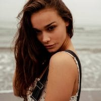 Beautiful brunette modeling on the beach wearing a white top giving a sexy look above her bare soulder