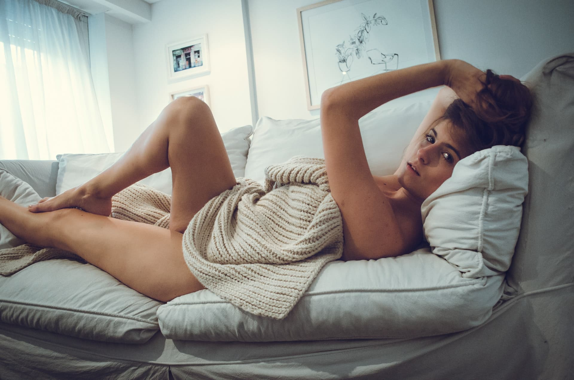 Beautiful woman posing in the nude on a sofa with a knitted sweater showing her body, thighs, legs and bare feet
