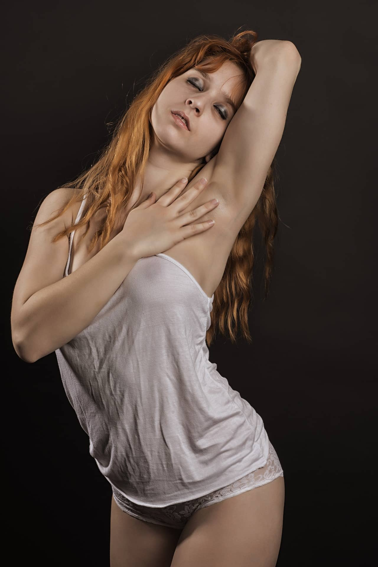 Beautiful redhead woman posing in an artistic photoshoot with her arm up wearing white transparent clothes and lace panties showing breast areola