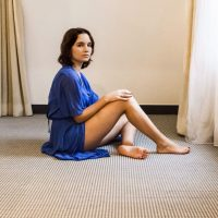 Beautiful woman all dressed in blue sitting bare foot on the ground showing her sexy legs and thighs