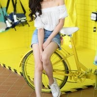 Beautiful asian woman sitting on a bicycle wearing a white top and denim shorts