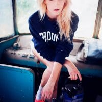 Beautiful blonde woman wearing white shorts and red sneakers in an old vehicle