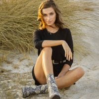 Beautiful woman sitting in the sand wearing a black dress and snake boots