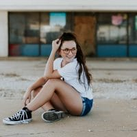 Beautiful and happy young woman wearing glasses, a NYC t-shirt and denim shorts sitting on the ground showing her bare legs
