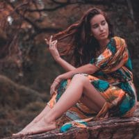 Beautiful woman with a colourful dress in a forest photoshoot