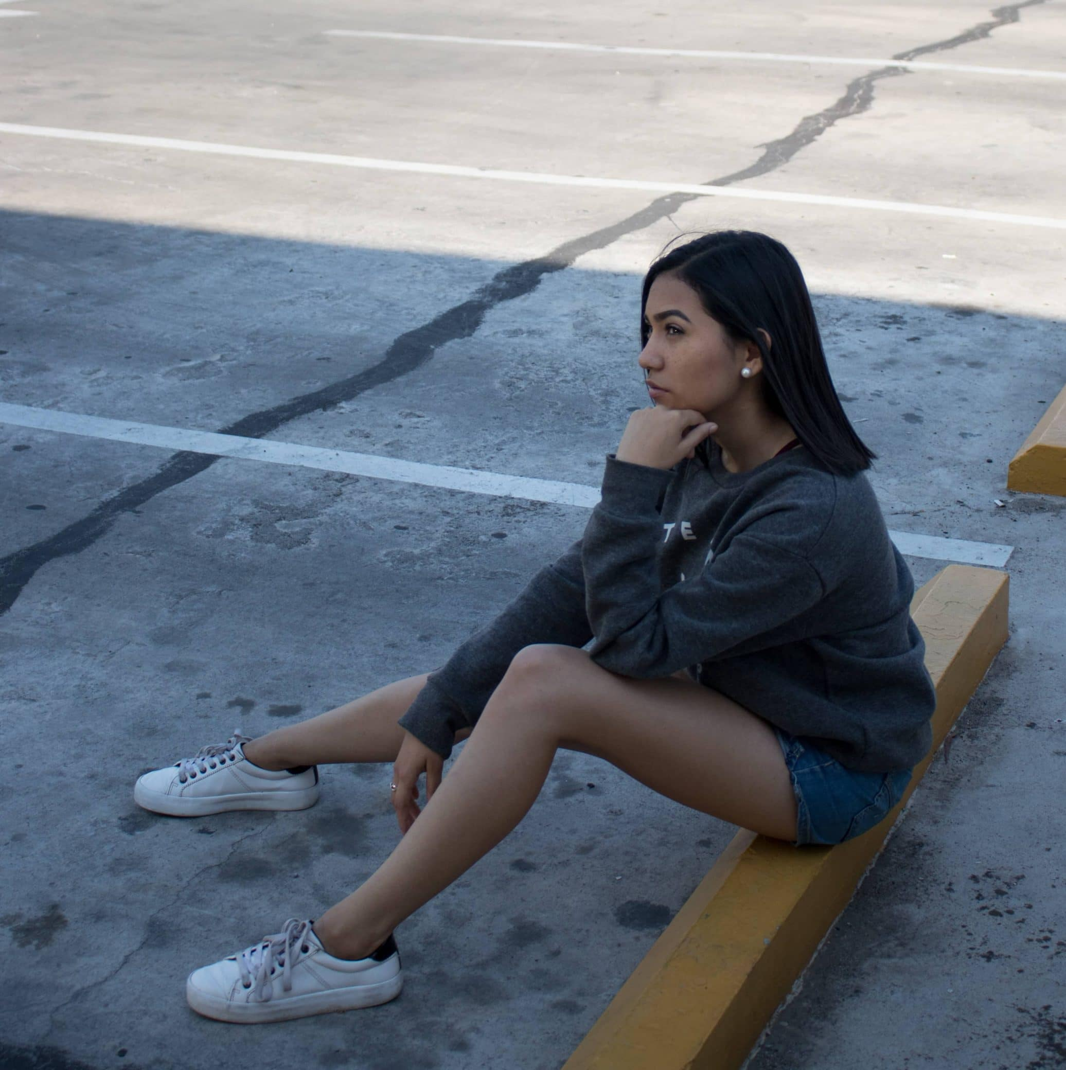 Beautiful woman sitting on concrete in a thinking pose thinking wearing sneakers and short denim shorts showing long bare legs and thighs