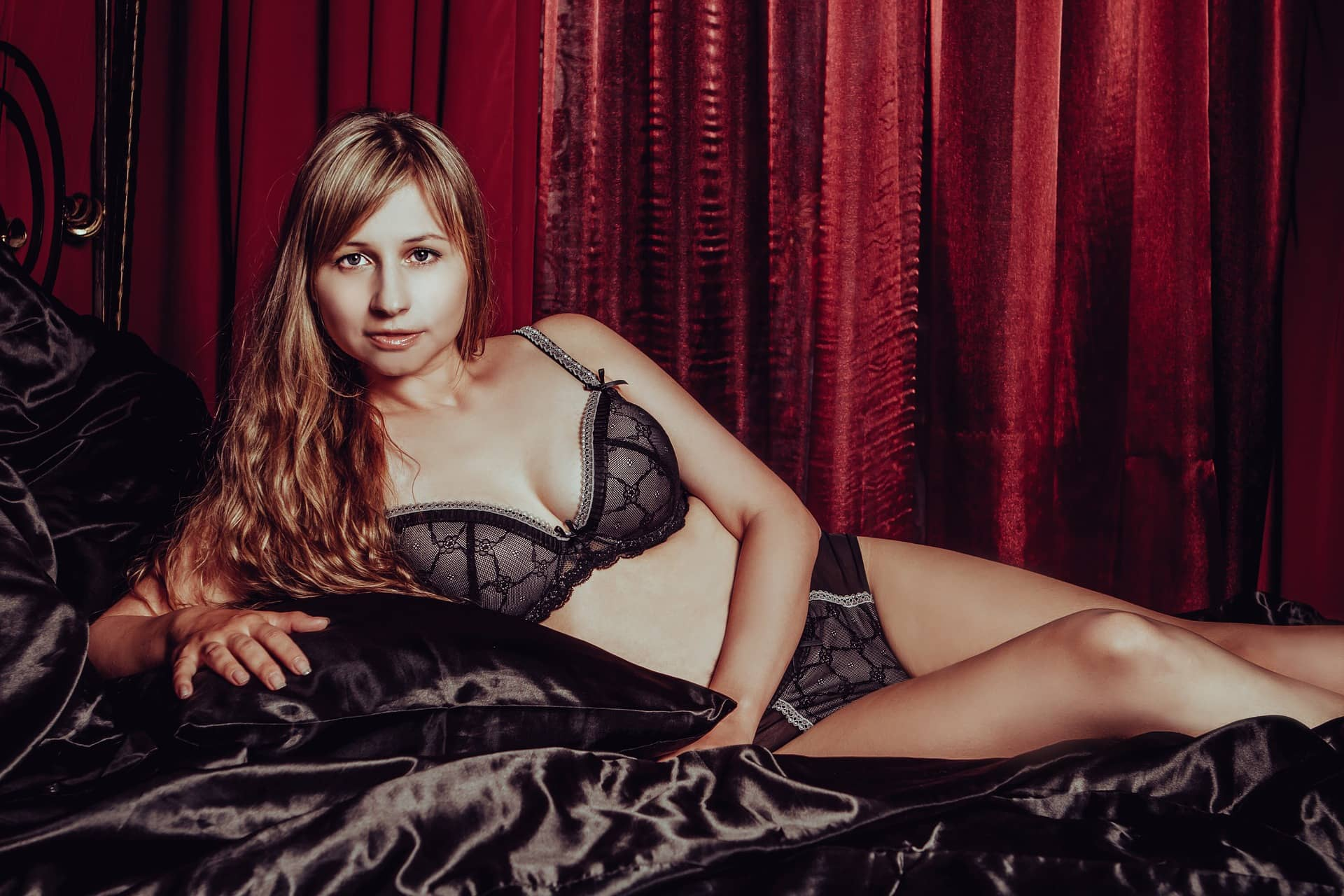 Beautiful russian woman Victoria Borodinova lying in a satin bed wearing black lace lingerie showing cleavage