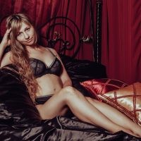 Beautiful woman on a satin sheets wearing black lace lingerie