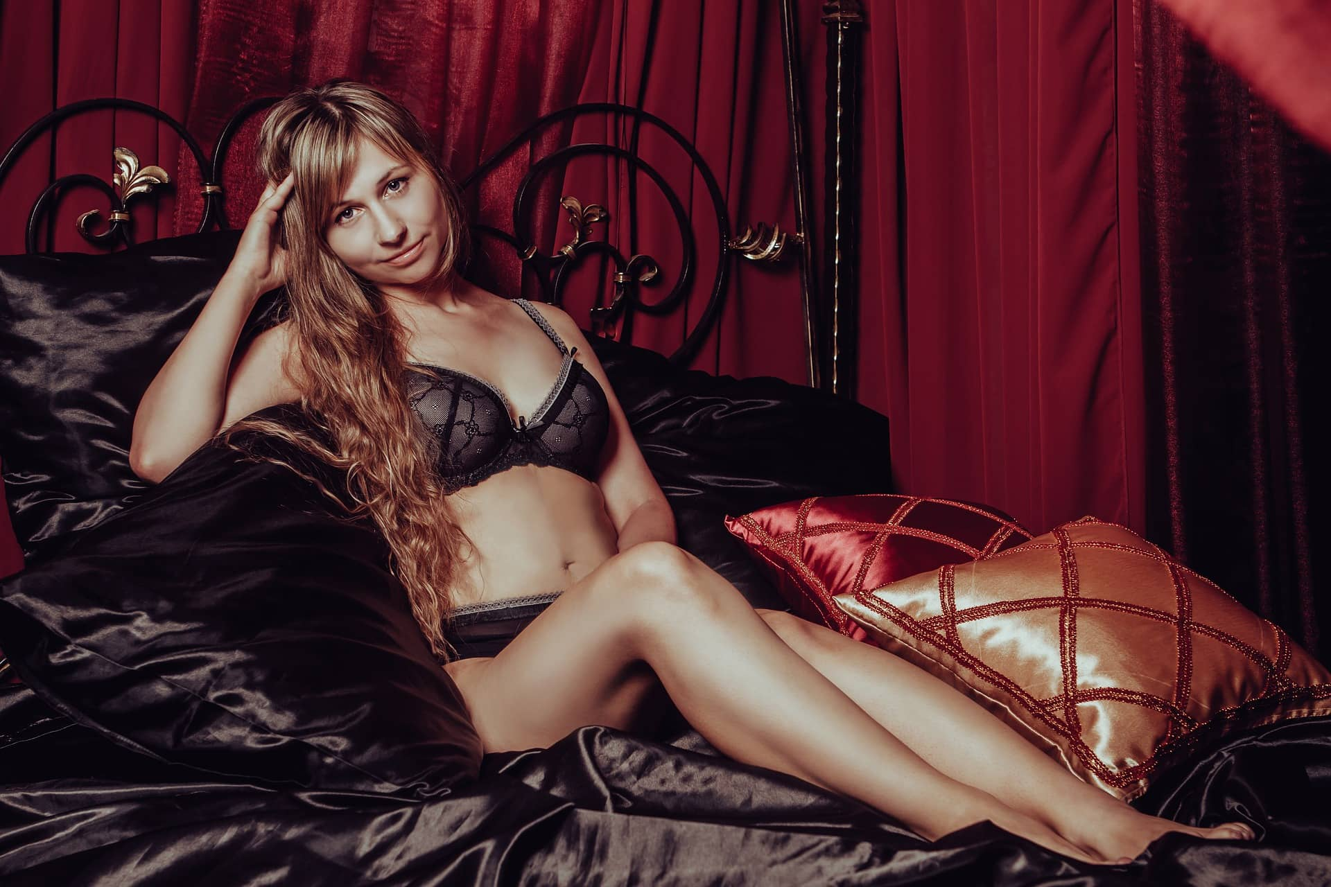 Beautiful russian woman Victoria Borodinova sitting in satin black sheets wearing black lace lingerie showing hew belly, thighs and sexy legs