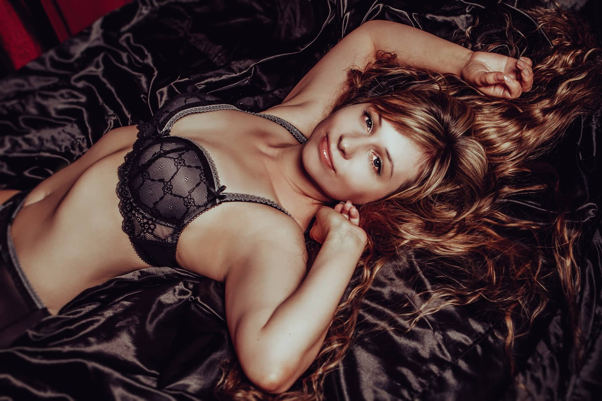 Beautiful russian woman Victoria Borodinova lying in her bed with her arms up wearing black lace lingerie showing her shaved armpits