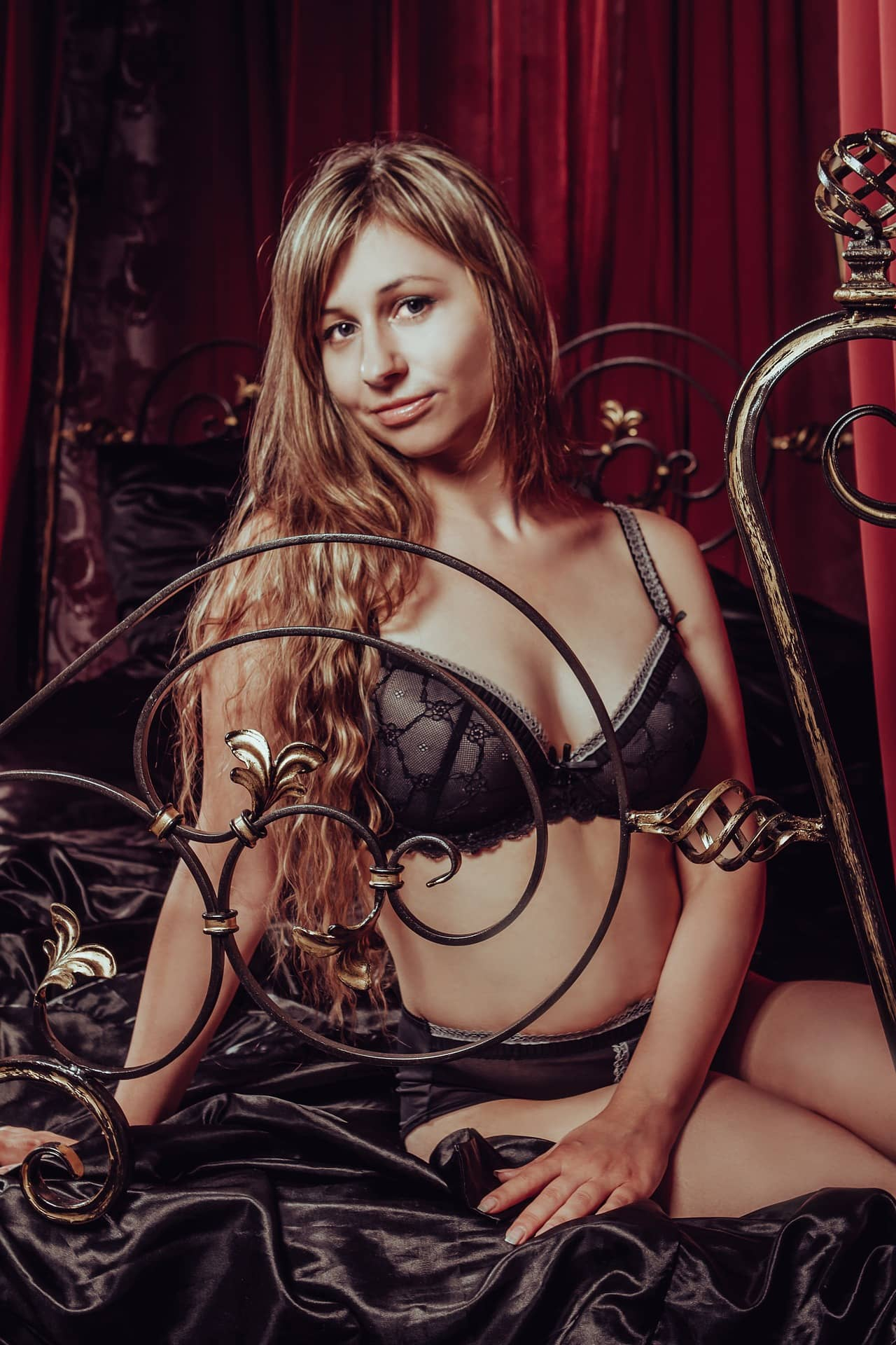 Beautiful russian woman Victoria Borodinova on a satin bed wearing black lace lingerie showing cleavage