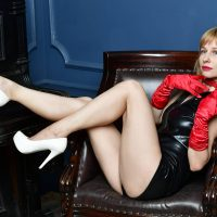 Beautiful blonde woman with long legs wearing a leather bodysuit , white heels and red gloves