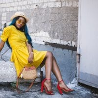 Beautiful women in a street photoshoot wearing a yellow dress and red heels