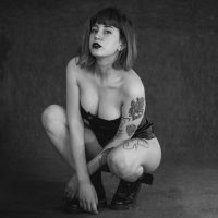 Beautiful tattooed woman wearing a black bodysuit and boots in a black and white photoshoot mid sitting showing cleavahe and bare legs