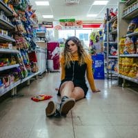 Beautiful blonde woman wearing black overall shorts for a photoshoot sitting on the floor in a supermarket showing her long sexy legs